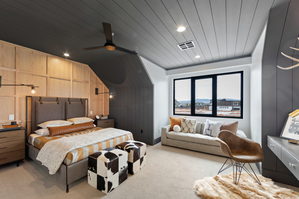 Bedroom with plush rug, cowhide ottomans and plaid bedspread
