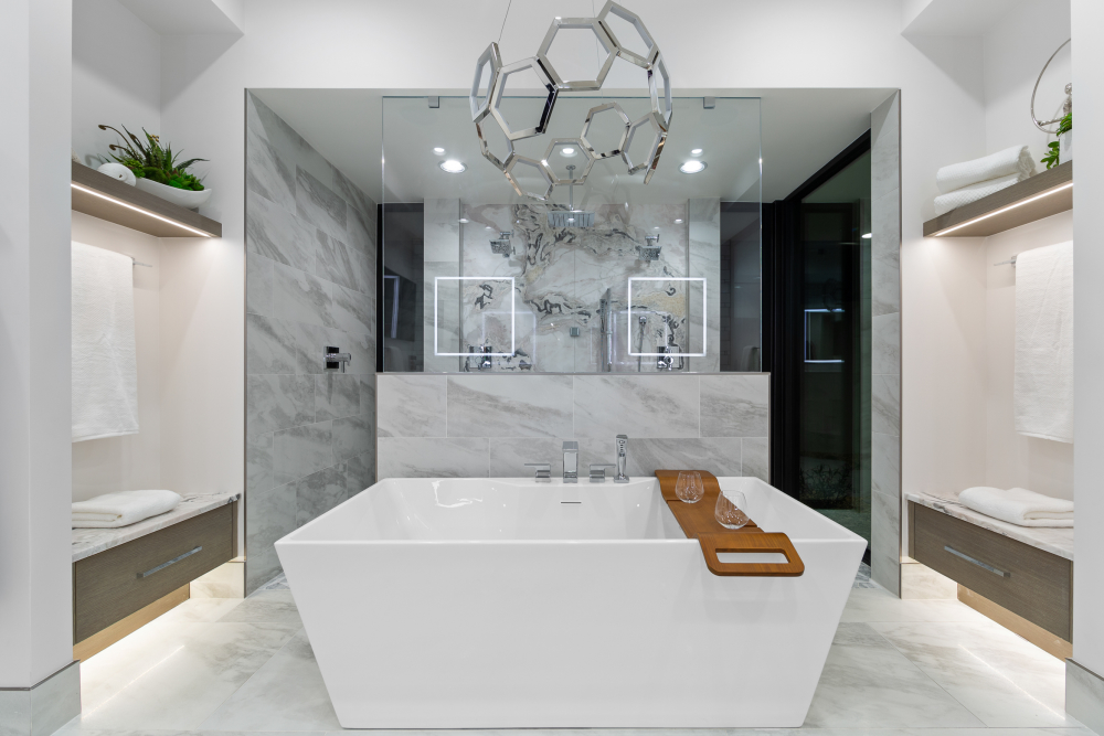 Spa bathroom with freestanding tub, light fixture and wooden bath caddy