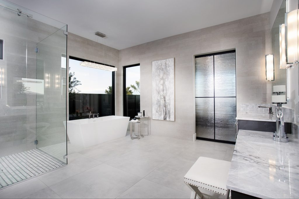 White-marble master bathroom with opaque glass door
