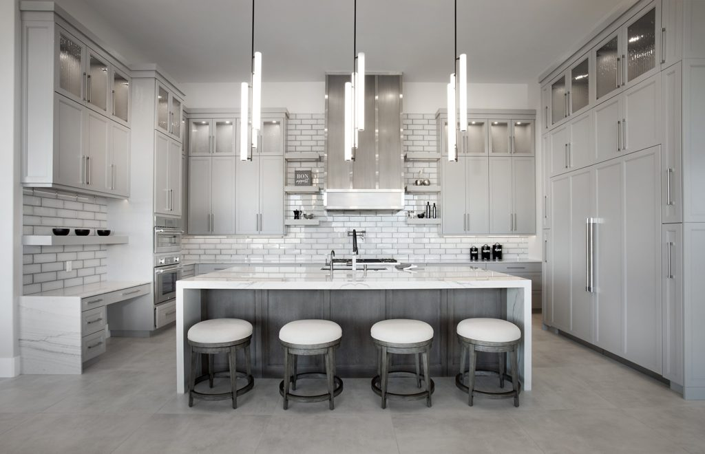 White kitchen with island, bar space, built-in desk and butler's pantry by Anderson Custom Homes
