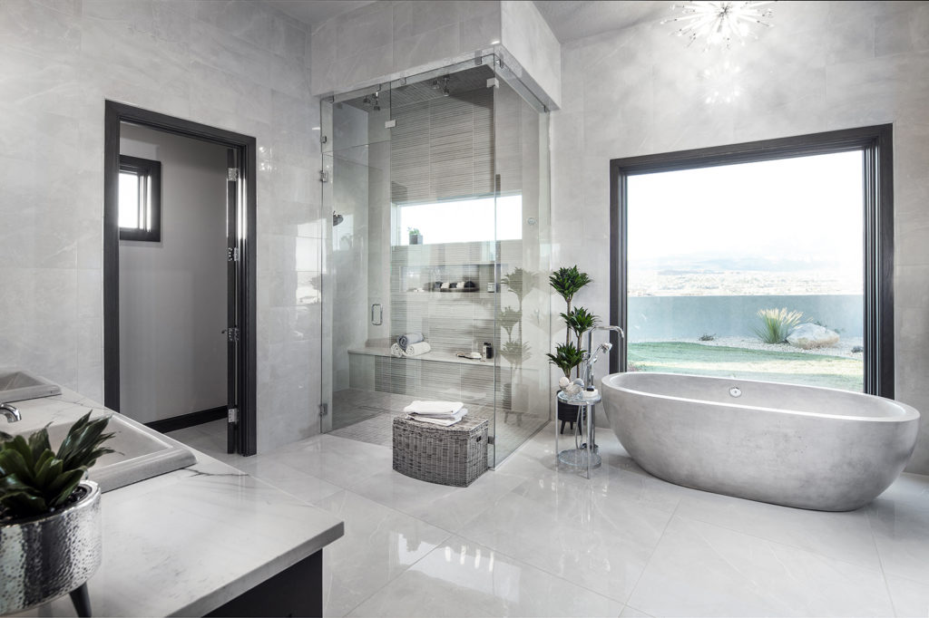 The master bathroom features an elegant soaking tub and walk-in shower designed by KH Traveller Custom Homes.