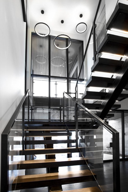 Open, lighted treads and steel-and-glass railing staircase